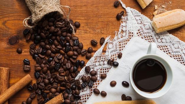 Tazza vicino a chicchi di caffè Foto Gratuite