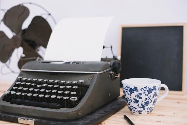 Tazza vicino alla retro macchina da scrivere Foto Gratuite