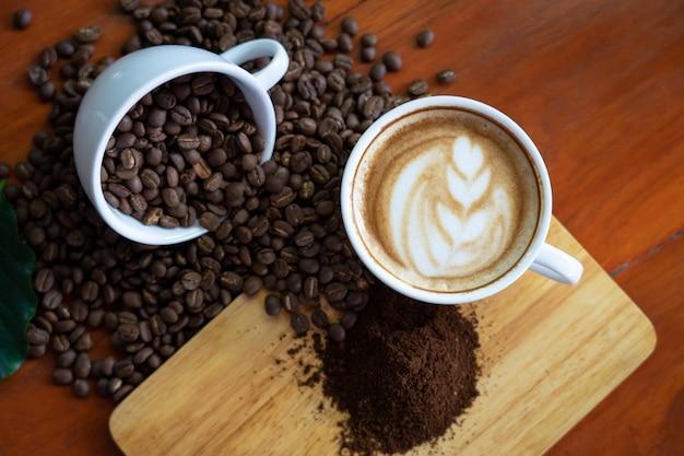 Tazze di caffè bianco e chicchi di caffè versato su un tavolo di legno, ben organizzato, Foto Premium