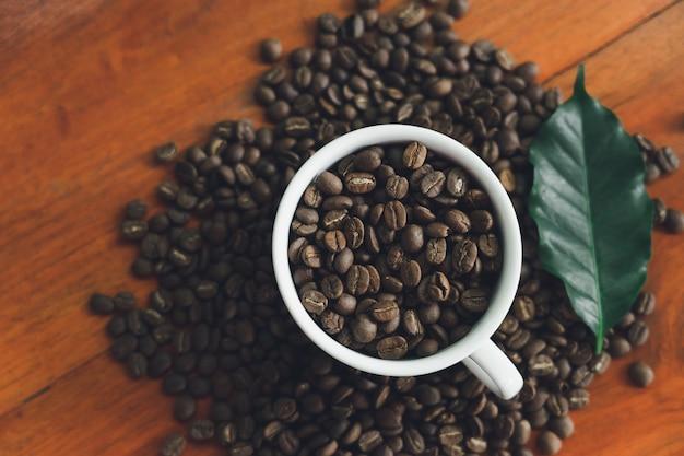 Tazze di caffè bianco e chicchi di caffè versato su un tavolo di legno, ben organizzato Foto Premium