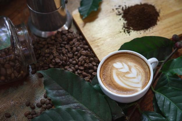 Tazze di caffè bianco e chicchi di caffè versato su un tavolo di legno, Foto Premium