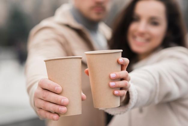Tazze di caffè defocused della tenuta delle coppie Foto Gratuite