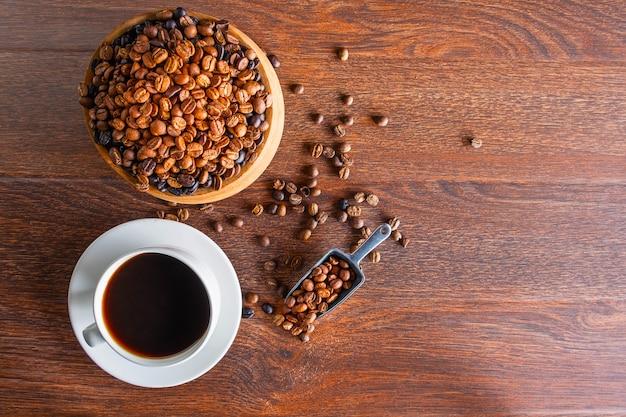 Tazze di caffè nero e chicchi di caffè tostati su un tavolo di legno Foto Premium