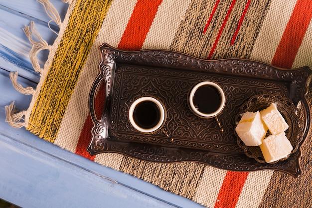Tazze di caffè vicino al piattino con dolci delizie turche sul vassoio contro tappetino Foto Gratuite
