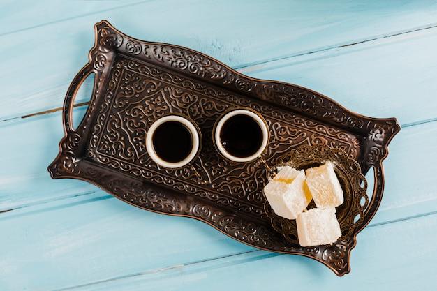Tazze di caffè vicino al piattino con dolci delizie turche sul vassoio Foto Gratuite