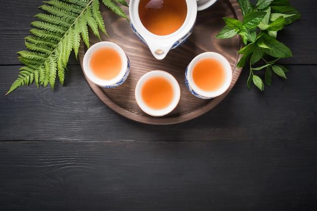 Tazze di tè e bollitore su sfondo scuro Foto Premium