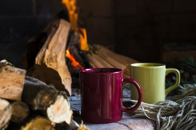 Tazze e coperta vicino al fuoco nel camino Foto Gratuite