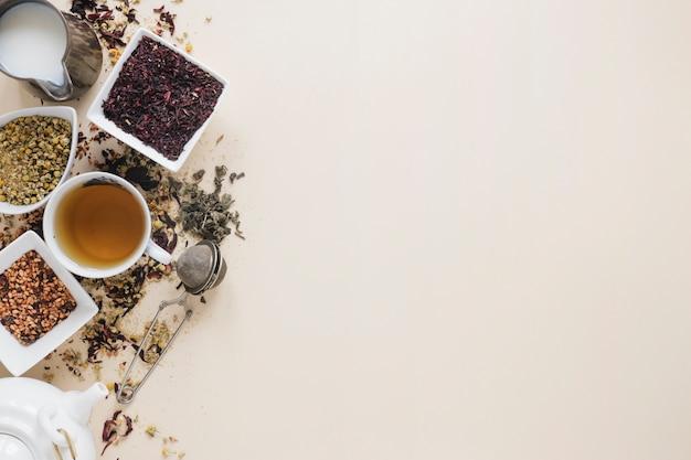Tè al limone con foglie di tè secche; fiori di crisantemo cinese essiccati; colino da tè; latte; erbe e teiera su sfondo colorato Foto Gratuite