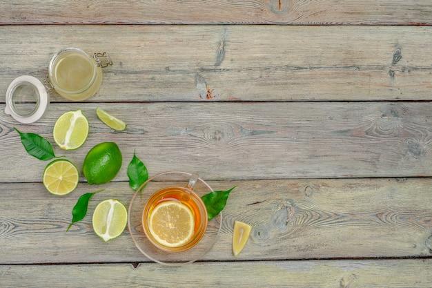 Tè al limone con limone e lime sul tavolo di legno dello sfondo Foto Premium
