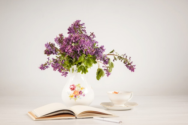 Tè al limone e bouquet di primule lilla sul tavolo Foto Gratuite