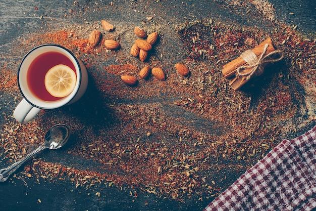 Tè al limone ed erbe secche con cannella secca, cucchiaio e mandorla piatta Foto Gratuite