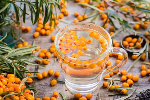Tè caldo con bacche di olivello spinoso in un bicchiere su un tavolo di legno Foto Premium