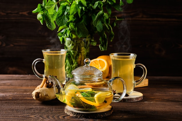 Tè caldo con limone, arancia, zenzero e menta sul tavolo di legno rustico al mattino Foto Premium