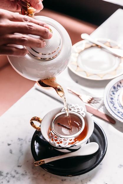 Tè caldo di mela servito versando dalla tazza attraverso un infusore per tè in acciaio inossidabile. Foto Premium