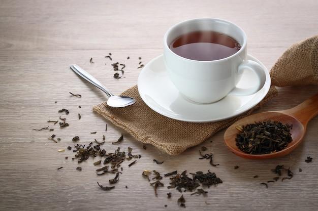 Tè caldo in vetro bianco posto su un tavolo di legno. Foto Premium