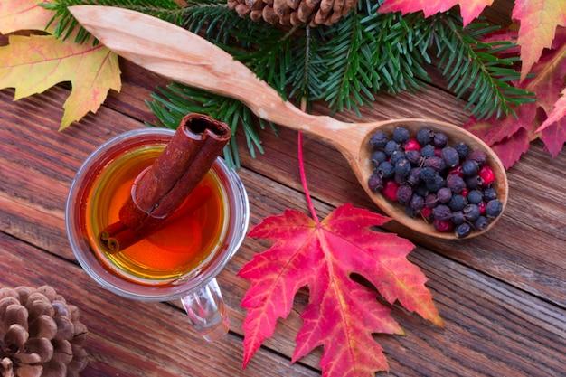 Tè con cannella e limone, foglie autunnali colorate di acero, bacche di biancospino in un cucchiaio di legno Foto Premium