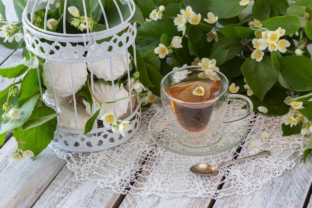 Tè con gelsomino e marshmallow in una gabbia decorativa bianca su un tavolo di legno bianco Foto Premium