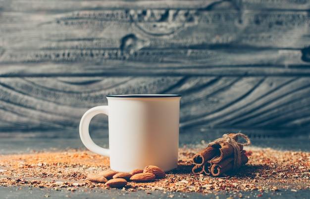 Tè ed erbe secche con cannella secca e mandorle sul tavolo di legno, vista laterale, Foto Gratuite