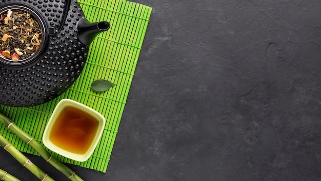 Tè ed erbe secche su placemat verde sopra superficie nera Foto Gratuite