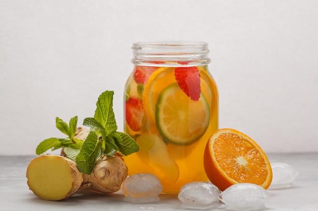 Tè freddo al gusto di zenzero con la menta in un barattolo di vetro, fondo bianco, spazio della copia. estate rinfrescante concetto di bevanda. Foto Premium