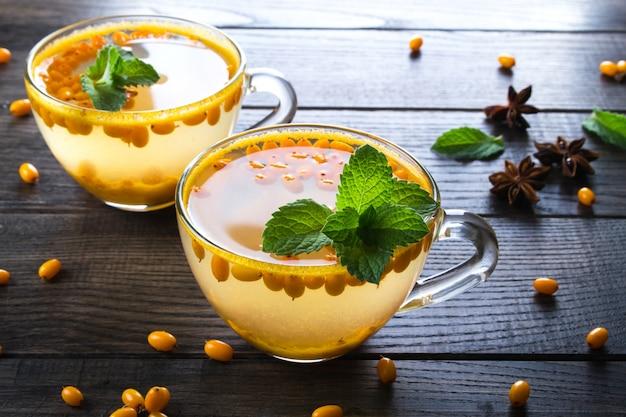 Tè naturale ai frutti di bosco con bacche fresche di olivello spinoso e menta sul tavolo scuro Foto Premium