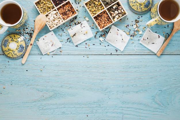 Tè nero fresco; varietà di erbe e bustina di tè disposti sul tavolo di legno Foto Gratuite