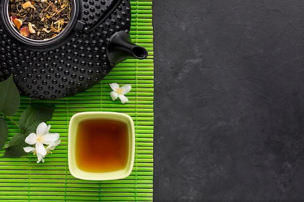 Tè sano con erbe secche e fiori di gelsomino bianchi su tovaglietta verde su sfondo nero Foto Gratuite