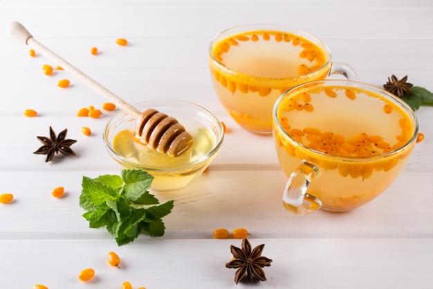 Tè sano dell'olivello spinoso della vitamina in tazze di vetro con le bacche fresche dell'olivello spinoso crudo e i bastoni di cannella, le stelle dell'anice, la menta e il miele su un tavolo da cucina bianco. Foto Premium