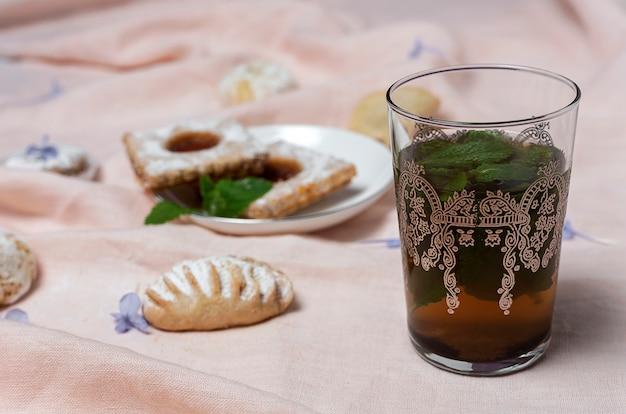 Tè tradizionale con menta e dolci arabi assortiti Foto Premium