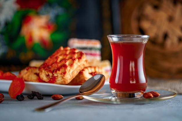 Tè turco in vetro tradizionale con dolci, frutta secca e noci per l'ora del the Foto Premium