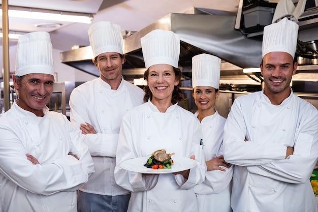 Team di chef con uno che presenta un piatto Foto Premium