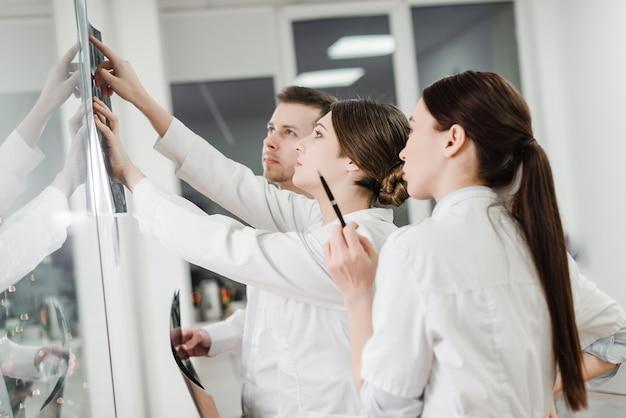 Team di medici che esaminano una radiografia di un paziente Foto Premium