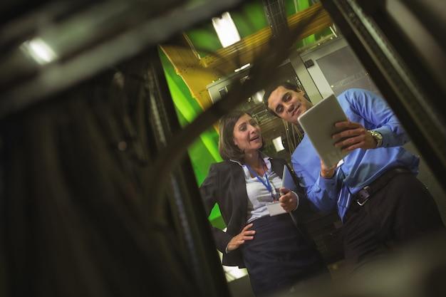 Tecnici che utilizzano la tavoletta digitale durante l'analisi del server Foto Premium
