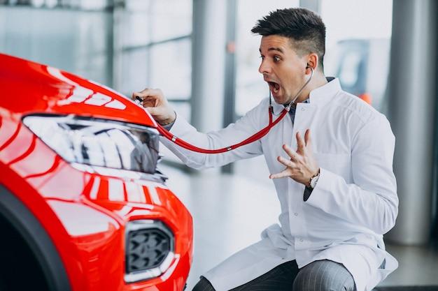 Tecnico auto con stetoscopio in un autosalone Foto Gratuite