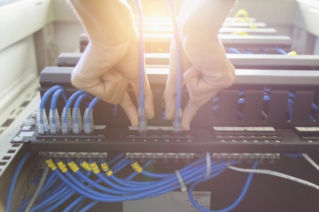 Tecnico che collega il cavo di rete per passare Foto Premium
