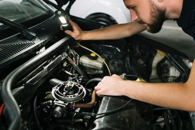 Tecnico che controlla il motore dell'automobile Foto Gratuite