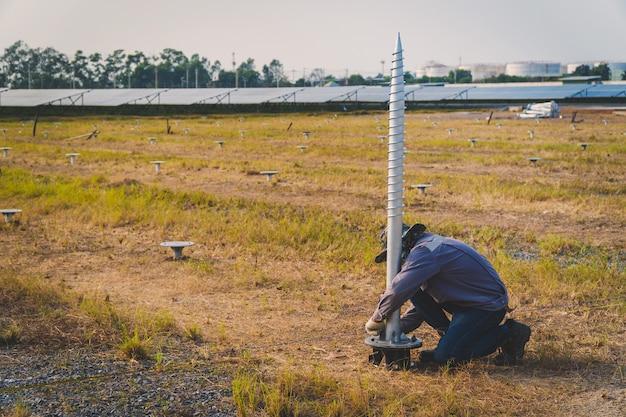 Tecnico che installa la vite di messa a terra per la struttura di montaggio del pannello solare nella fattoria solare Foto Premium