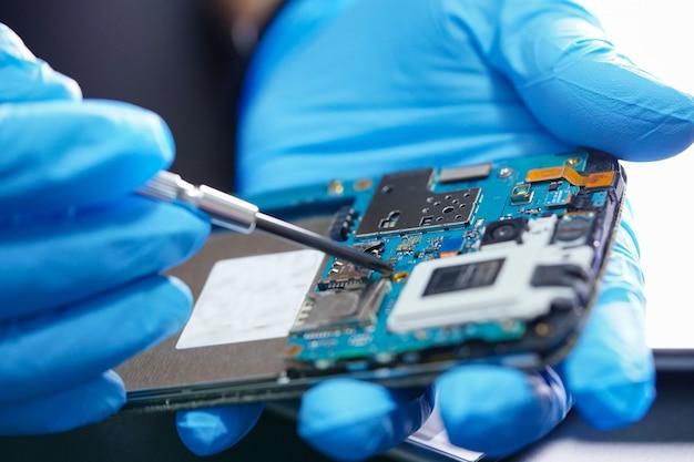 Tecnico che ripara la scheda principale del micro circuito dello smartphone. Foto Premium