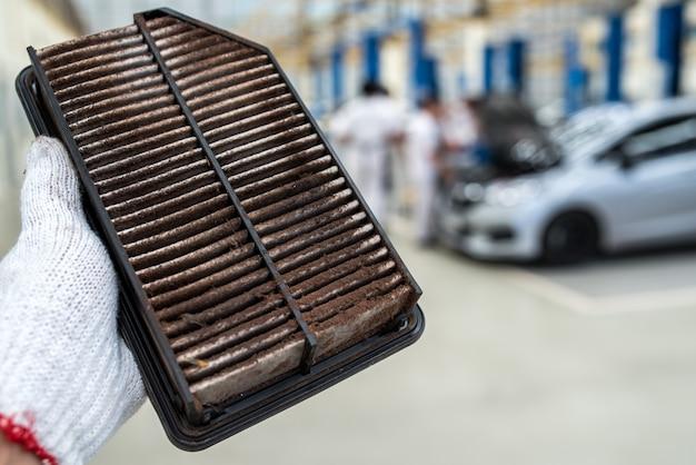 Tecnico che tiene il filtro dell'aria sporco per l'automobile Foto Premium