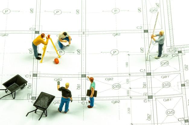 Tecnico geometra persone in miniatura sta misurando la distanza per costruire una casa. Foto Premium