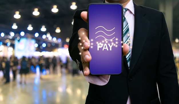 Tecnologia di blockchain della moneta di libra dello smartphone di manifestazione dell'uomo d'affari Foto Premium
