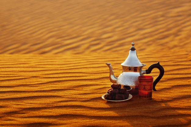 Teiera araba, tazza e datteri stanno sulla sabbia nel deserto Foto Premium