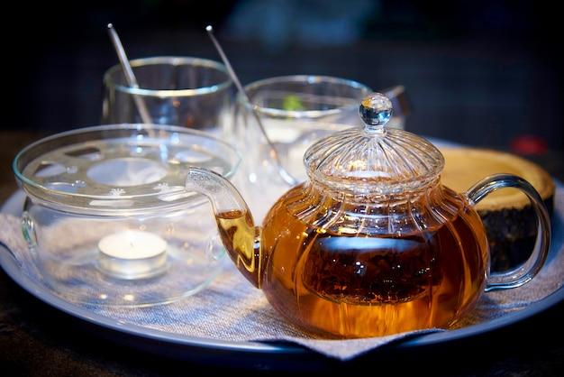 Teiera di vetro con tè su un vassoio con il primo piano tazze. Foto Premium