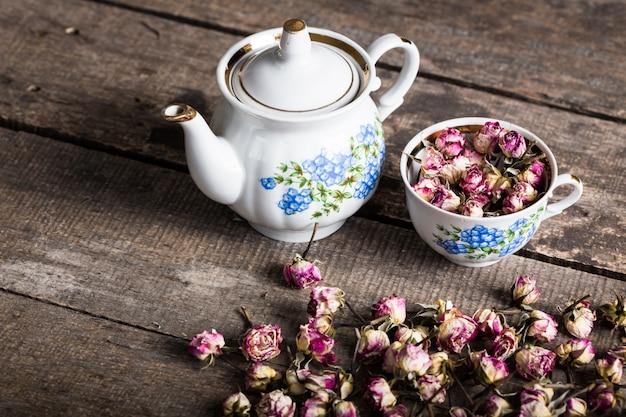 Teiera e tazza d'annata con i fiori di fioritura del tè su legno Foto Premium