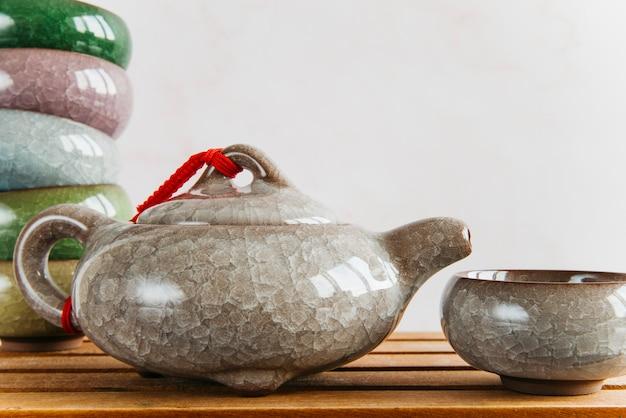 Teiera e tazze di tè ceramiche cinesi sullo scrittorio di legno contro la parete Foto Gratuite