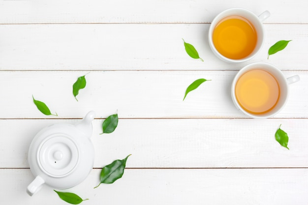 Teiera e tazze di tè su un bianco in legno Foto Premium