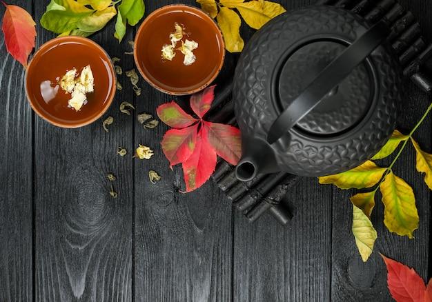 Teiera e tè verde neri con il gelsomino in una tazza dell'argilla, su un nero e di legno con la vista superiore dell'alimento delle foglie di autunno Foto Premium