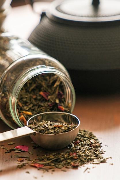 Teiera nera e una bottiglia di tè verde biologico su un tavolo di legno Foto Premium