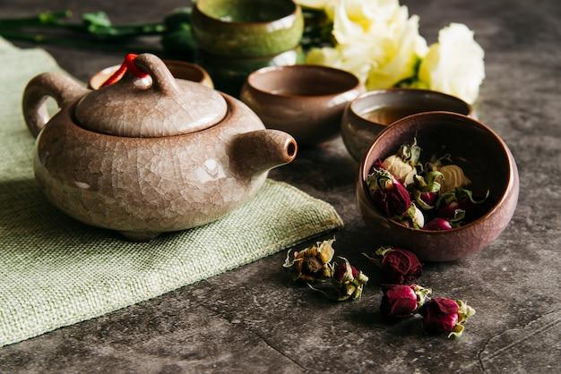 Teiera tradizionale in ceramica con tazze da tè e rosa appassita su fondo in cemento Foto Gratuite