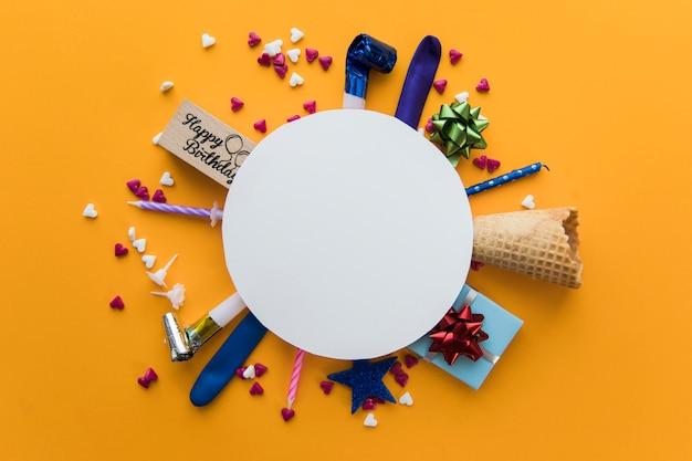 Telaio bianco rotondo bianco sopra il ventilatore del partito; pacco regalo; candele; spruzza e cono di cialda su uno sfondo di colore arancione Foto Gratuite